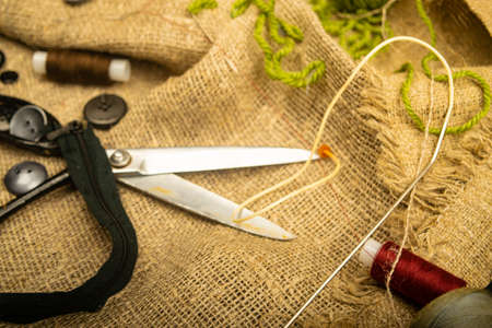 Buttons of various sizes, a spool of thread, tailor's scissors, and a zipper on rough-textured burlap. Close up