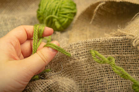 The girl stitches together pieces of coarse-textured burlap with green threads. Close up