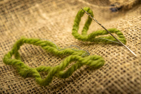 Stitches of green thread on the burlap with a rough texture. Close up