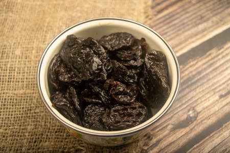 Dried prunes in a metal bowl on a wooden background. Close up
