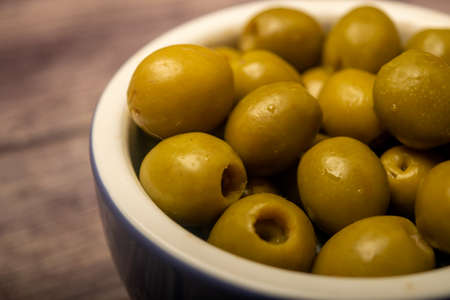 Green olives in a ceramic bowl on a wooden background . Close up