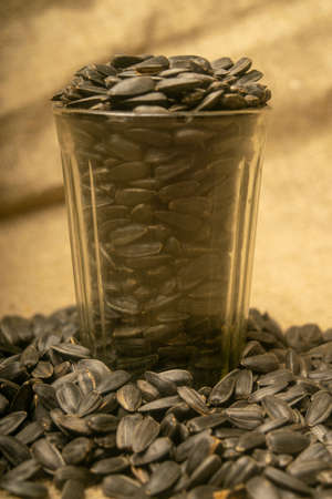 Roasted seeds of sunflower in faceted glass and a scattering of seeds on the background burlap with a rough texture. Close up Standard-Bild