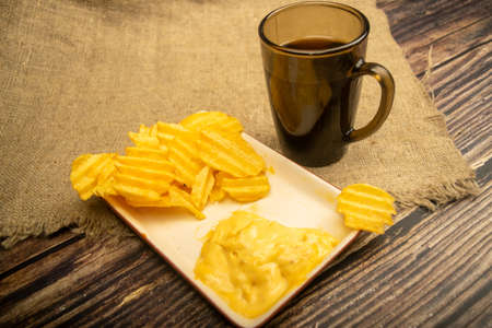 Potato chips with cheese sauce and a coffee mug on a wooden background. Close up Standard-Bild