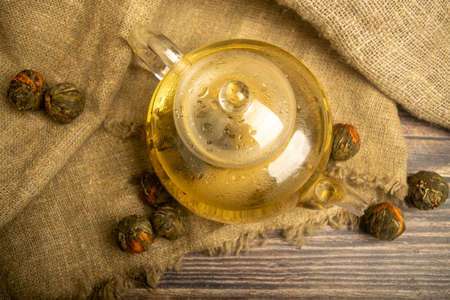 Flower tea brewed in a glass teapot on a background of homespun fabric with a rough texture. Close up Standard-Bild