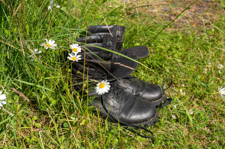 Old leather Hiking boots in the green grass. Summer is a time of travel. Close up