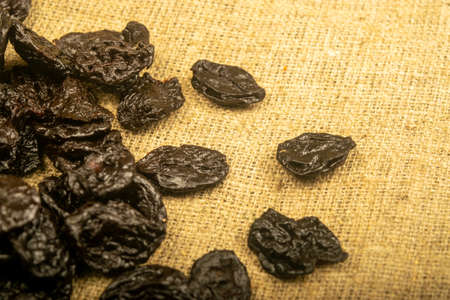 Dried prunes in bulk on burlap with a rough texture. Close up