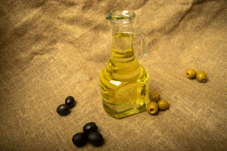 A glass bottle of olive oil on a background of green olives, black olives and homespun fabric with a rough texture. Close up