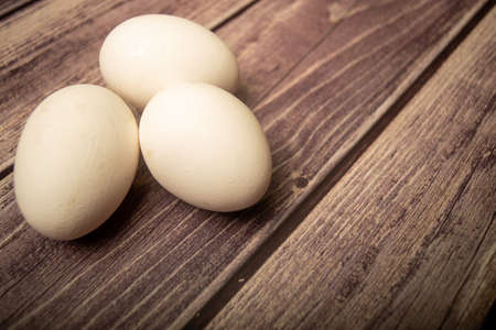 White chicken eggs on a wooden background. Close up