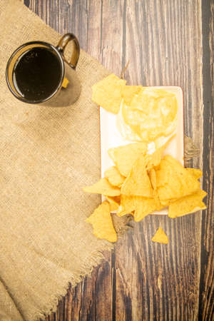 Corn chips with cheese sauce and a coffee mug on a wooden background. Close up