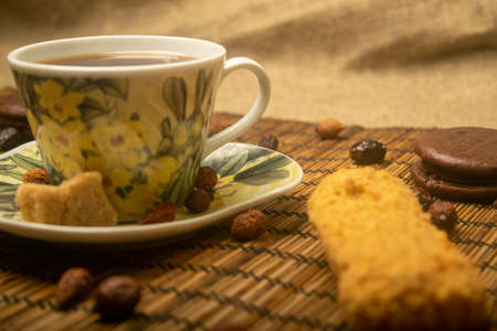 A Cup of tea, dried rosehip fruit, pieces of brown cane sugar, and cookies on a reed Mat. Close up
