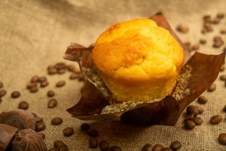 Fresh cupcake, coffee beans and chocolate on a homespun fabric with a rough texture. Close up