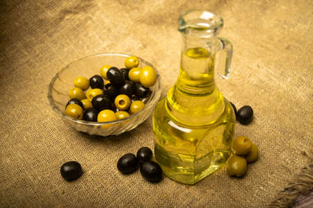 A glass bottle of olive oil on a background of green olives, black olives and homespun fabric with a rough texture. Close up Standard-Bild