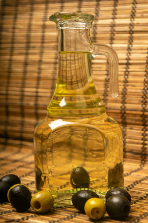 A bottle of olive oil on a background of green olives, black olives and a reed Mat. Close up Standard-Bild