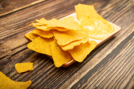 Corn chips with cheese sauce on a wooden background. Close up