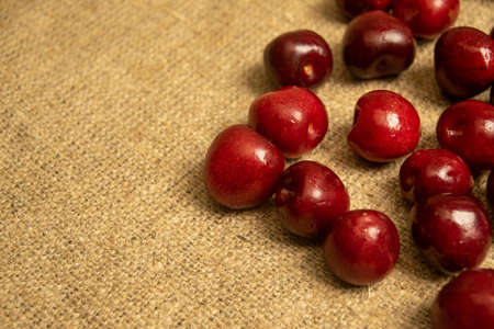Ripe juicy cherries scattered on a homespun fabric with a rough texture. Close up