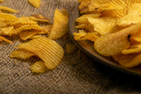Fluted potato chips on a background of homespun fabric with a rough texture. Close up