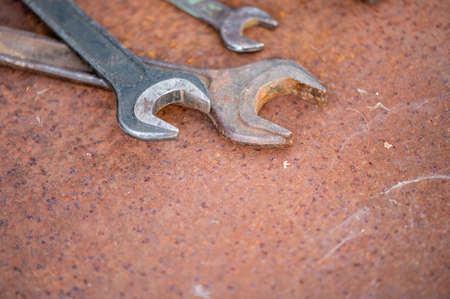 Old wrenches on a rusty sheet of metal, close-up, selective focus Imagens
