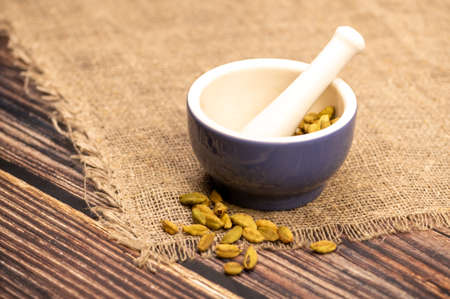 Cardamom in a ceramic mortar and pestle, close-up, selective focus