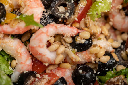 Vegetable salad with prawns and pine nuts on a plate. Homemade food. Close up