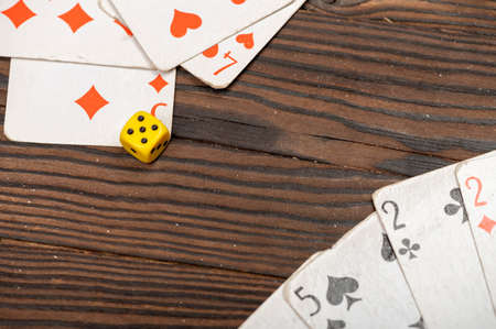 Playing cards and dice on a wooden table. Close-up, selective focus.