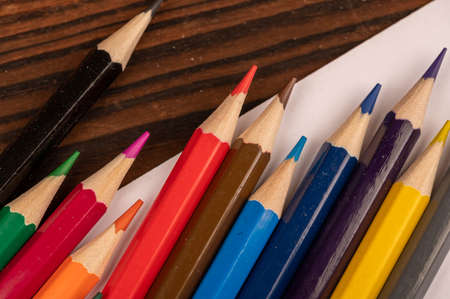 Colorful pencils and white sheets of paper on a wooden table. Close-up selective focus. 写真素材