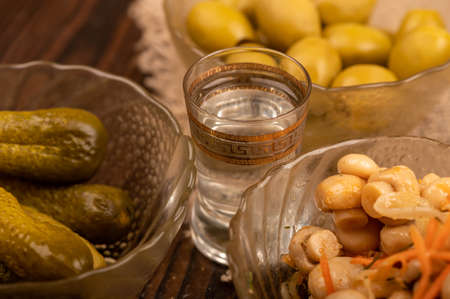 A glass of vodka and pickled cucumbers, salted mushrooms and salted olives in glass dishes on a background of homespun fabric with a rough texture. Close-up Selective focus