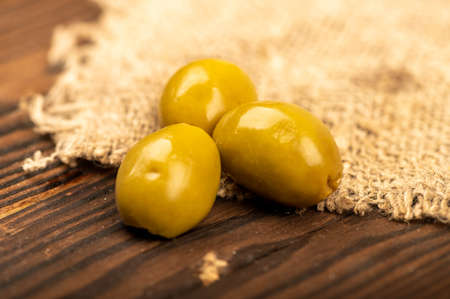 Salted olives on a wooden table. Close-up Selective focus