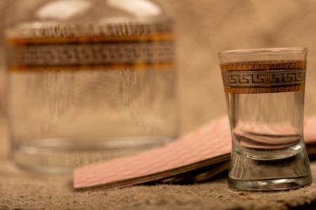 A glass decanter with vodka and a glass of vodka on the background of a homespun fabric with a rough texture. Close-up Selective focus 写真素材