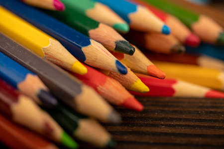 Colored pencils on a wooden table. Close-up, selective focus. Self-development during self-isolation in the   pandemic.