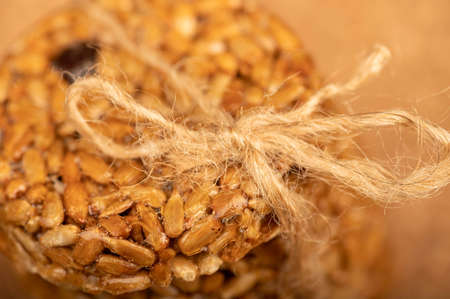 Homemade cookies with sunflower seeds and raisins, tied with string on a wooden table. Close-up Selective focus