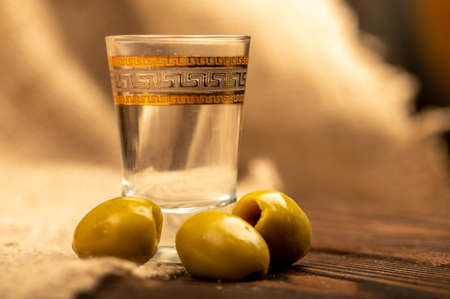 A glass of vodka and salted olives on a background of homespun fabric with a rough texture. Close-up Selective focus