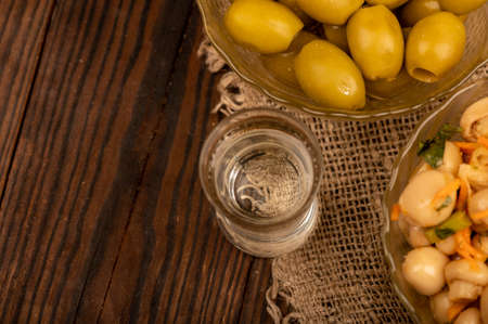 A glass of vodka and salted mushrooms and salted olives in glass dishes on a background of homespun fabric with a rough texture. Close-up Selective focus