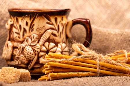 Breadsticks with salt tied with string and an earthenware mug for tea. Close-up Selective focus 写真素材