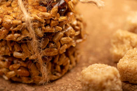 Homemade cookies with sunflower seeds and raisins tied with string and pieces of brown cane sugar on a wooden table. Close-up Selective focus