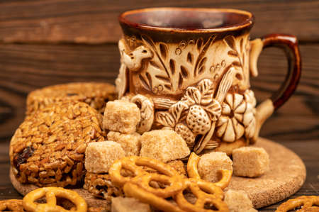 Homemade cookies with sunflower seeds and raisins, pieces of brown cane sugar, shaped breadsticks and an earthenware mug of tea on a wooden table. Close-up Selective focus