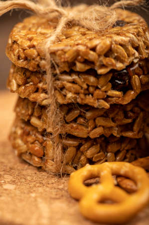 Homemade cookies with sunflower seeds and raisins tied with twine and curly breadsticks on a wooden table. Close-up Selective focus