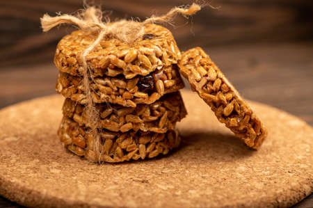 Homemade cookies with sunflower seeds and raisins tied with string on a wooden table. Close-up Selective focus