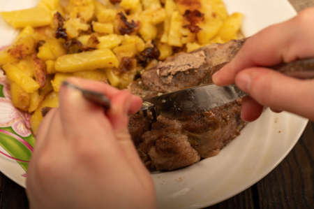 Someone is cutting a piece of juicy roast meat on a plate of fried potatoes with a knife and fork. Close-up Selective focus