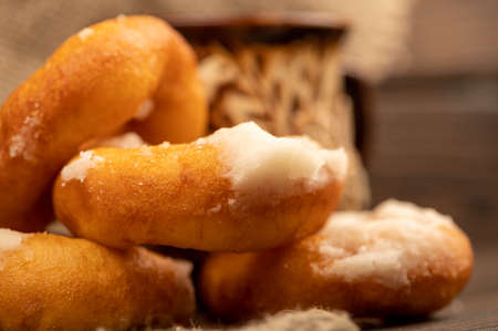 Fresh homemade donuts with powdered sugar and a earthenware mug of tea. Close-up Selective focus