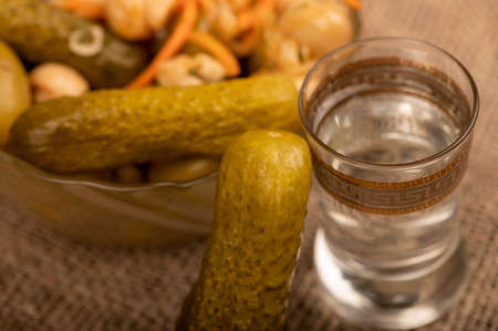 A glass of vodka, pickled cucumbers and salted mushrooms in a glass dish on a background of homespun fabric with a rough texture. Close-up Selective focus