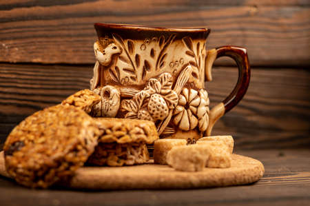 Homemade cookies with sunflower seeds and raisins, pieces of brown cane sugar and an earthenware mug of tea on a wooden table. Close-up Selective focus