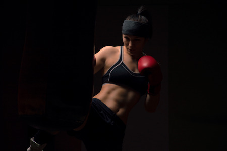 A boxer girl wearing red gloves and a bandana is hitting the bag
