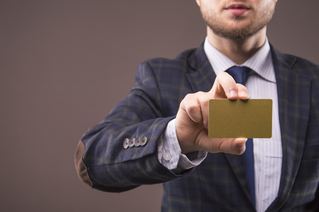 Handsome man in a suit holding a business card gold color