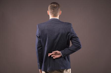 Businessman fingers crossed behind his back