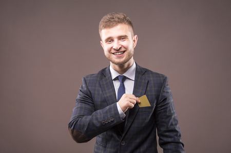 Charismatic man in a suit smiles and puts the card into his breast pocket Stock Photo
