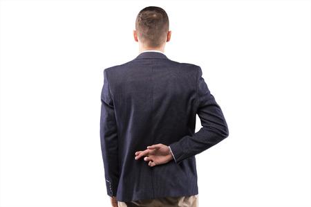 Zakenmanvingers gekruist achter zijn rug Stockfoto
