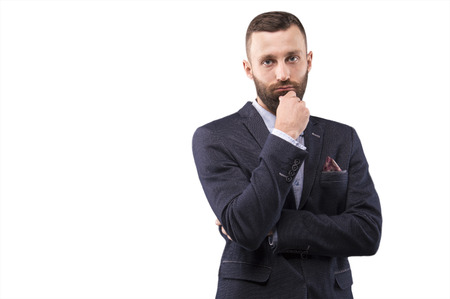 Confident man leaned his hand to his beard and looking at the camera Stock Photo