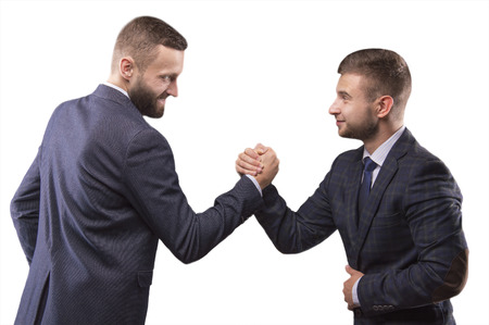 wrestle: Two men in suits struggling in his arms looking into each others eyes Stock Photo
