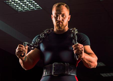 Huge weightlifter with a chain around his neck is in the gym