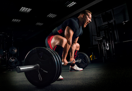 Athlete screams in the gym to motivate himself to perform an exercise called deadlift Archivio Fotografico